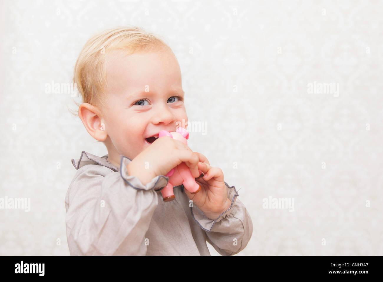 Retrato de un sonriente niño sosteniendo un juguete rosa Foto de stock