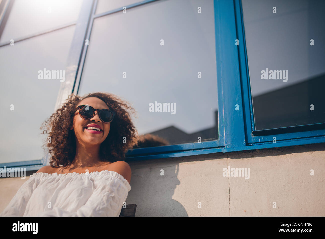 Disparo de feliz joven africana sentado afuera mirando lejos y sonriente. Mujer con gafas de sol sentado afuera Imagen De Stock