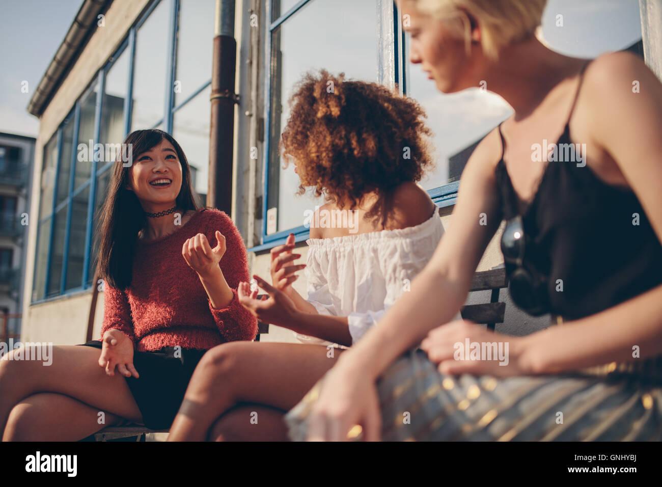 Grupo multiétnico de amigas sentados afuera y hablar. Las mujeres jóvenes sentados en el balcón. Imagen De Stock