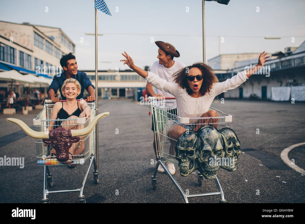 Jóvenes amigos divirtiéndose en un carrito de la compra. Los jóvenes multiétnica racing en compras. Imagen De Stock
