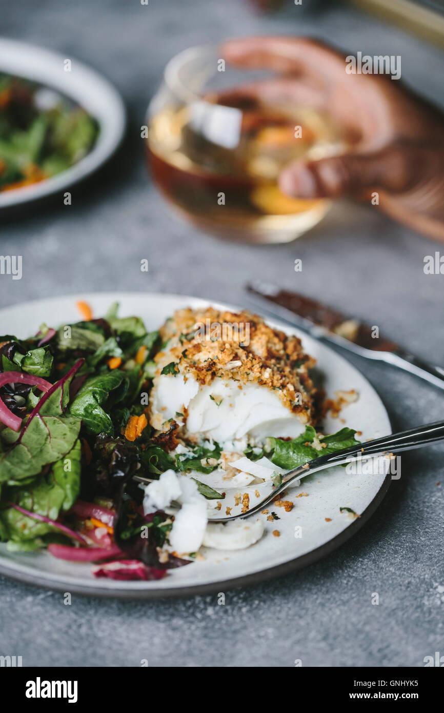 Una mitad comido pescado frito junto con ensalada es fotografiado desde el lateral. Imagen De Stock