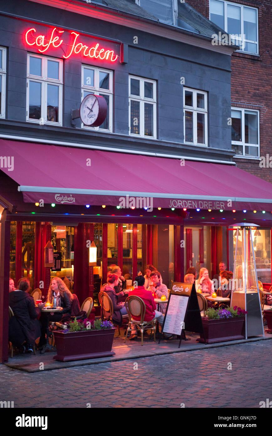 Los comensales comer al fresco en el Cafe Jorden, un pavimento cafetería Plaza Torvet en Lille en el antiguo Barrio Latino de Aarhus, Dinamarca Foto de stock