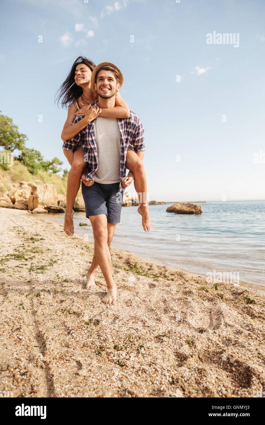 Guapo sonriente joven dando piggy back paseo a su novia en la playa. Imagen De Stock