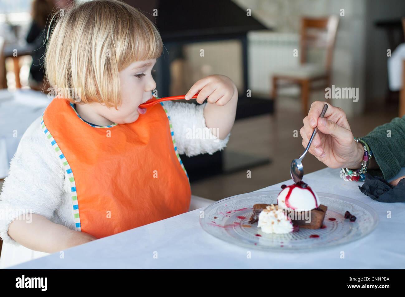 Dos años kid comer con cuchara de plástico naranja un trozo de pastel de chocolate con helado de vainilla Imagen De Stock