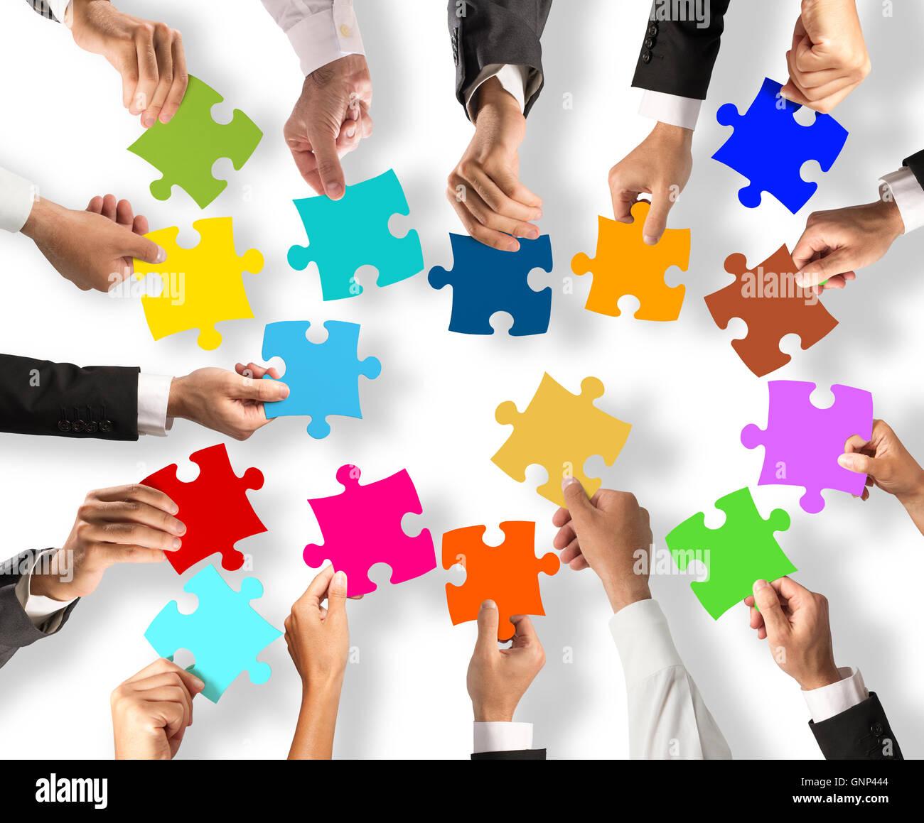 El trabajo en equipo y el concepto de integración con piezas de rompecabezas Imagen De Stock