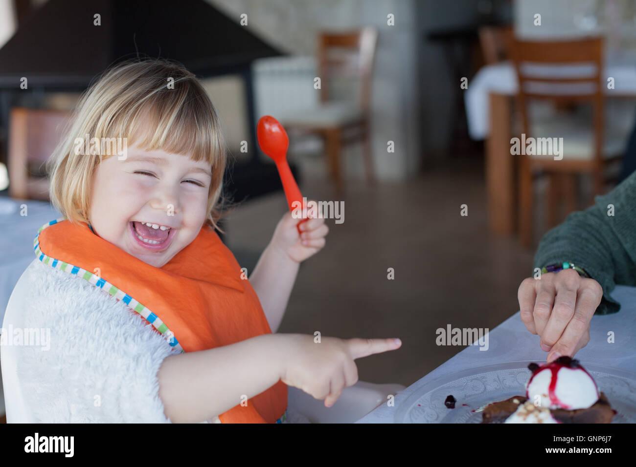 Dos años divertidas y niño feliz con cuchara de plástico naranja y bib riendo y señalando con Imagen De Stock
