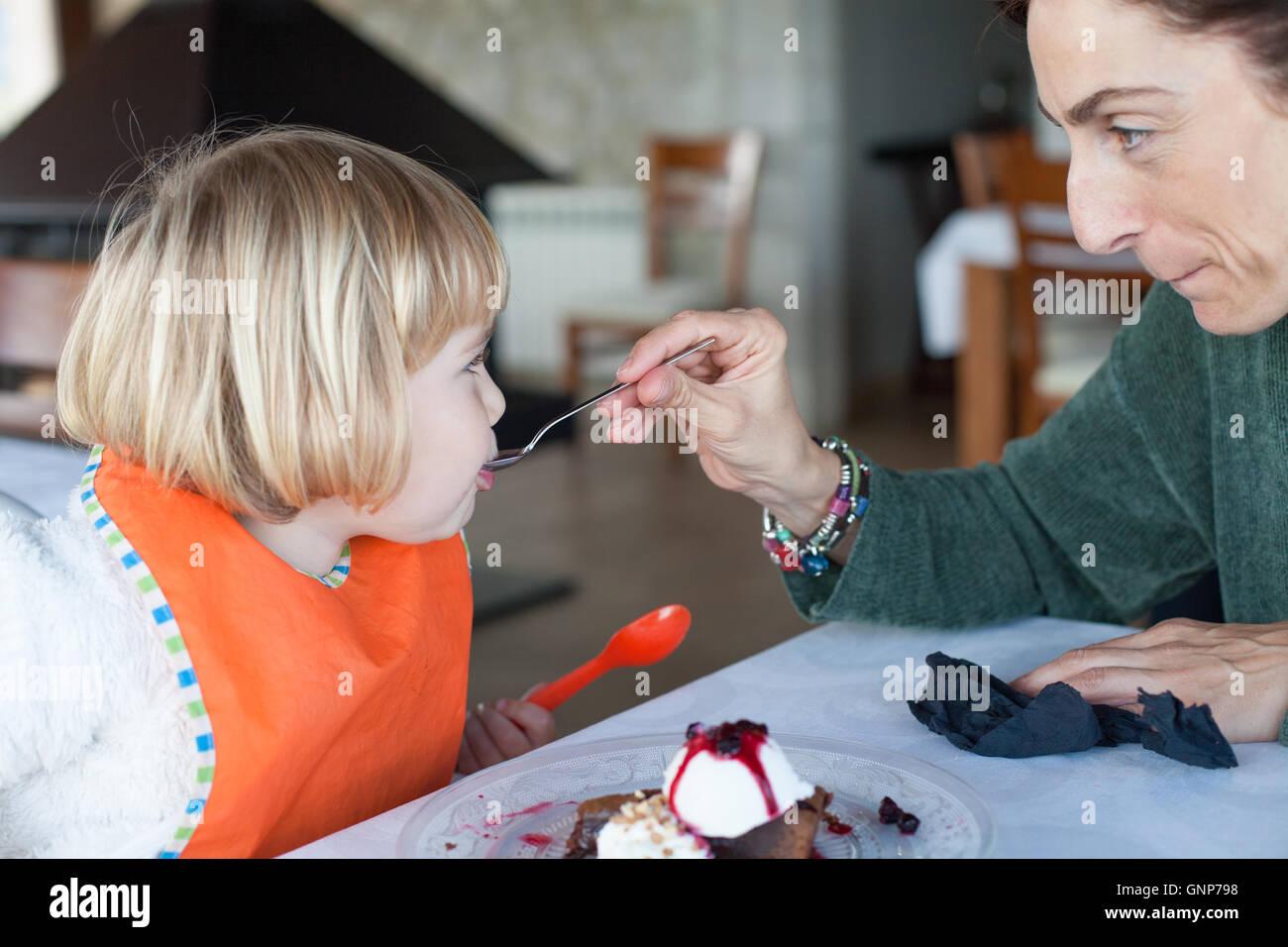 Suéter verde de alimentación mujer chico naranja babero con cuchara de metal un trozo de pastel de chocolate Imagen De Stock