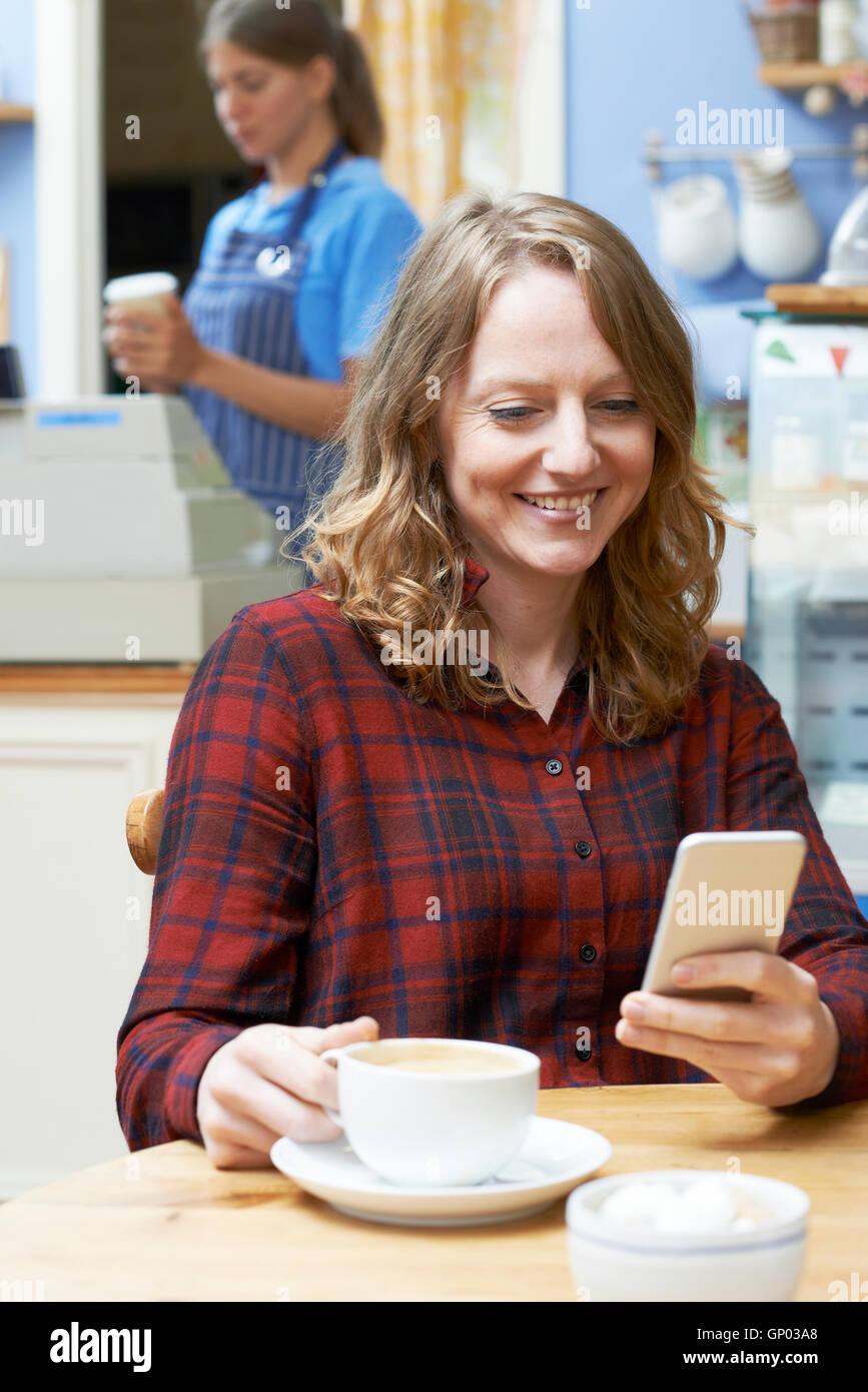 Mujer en una cafetería leyendo un mensaje de texto en el teléfono móvil Imagen De Stock