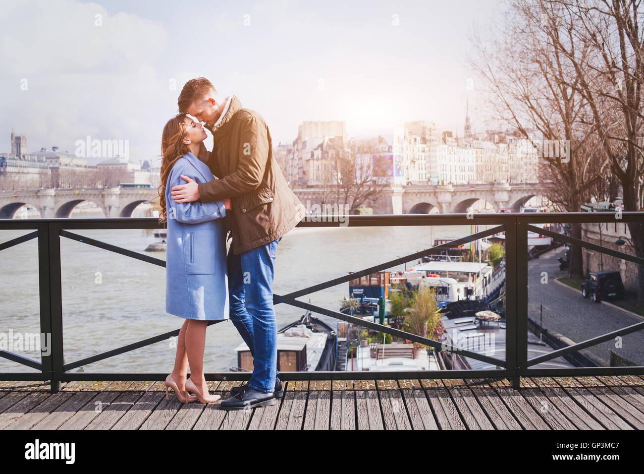Fecha romántica, la joven pareja besándose en el puente en París Imagen De Stock