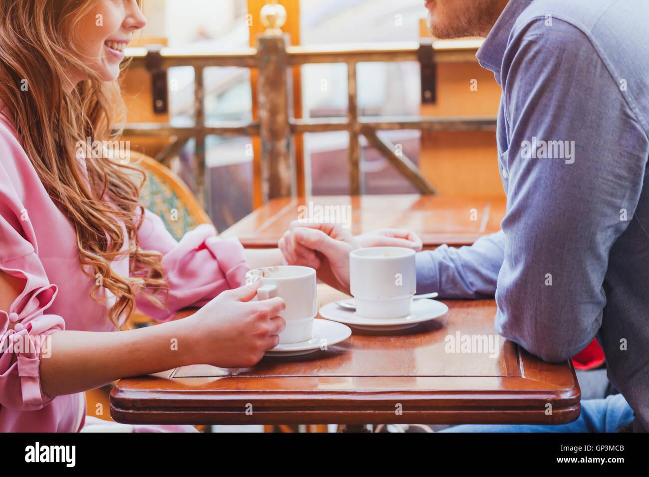 Dating, las manos de la pareja en la acogedora cafetería, bebiendo café Imagen De Stock