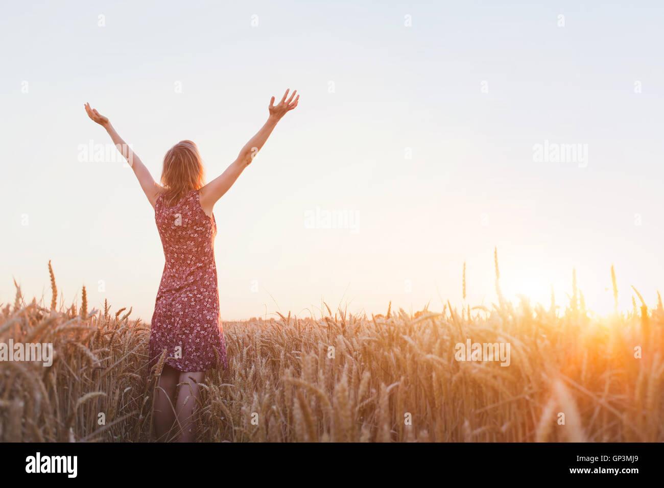 La respiración, mujer con manos alzadas disfrutando del atardecer en el campo Imagen De Stock