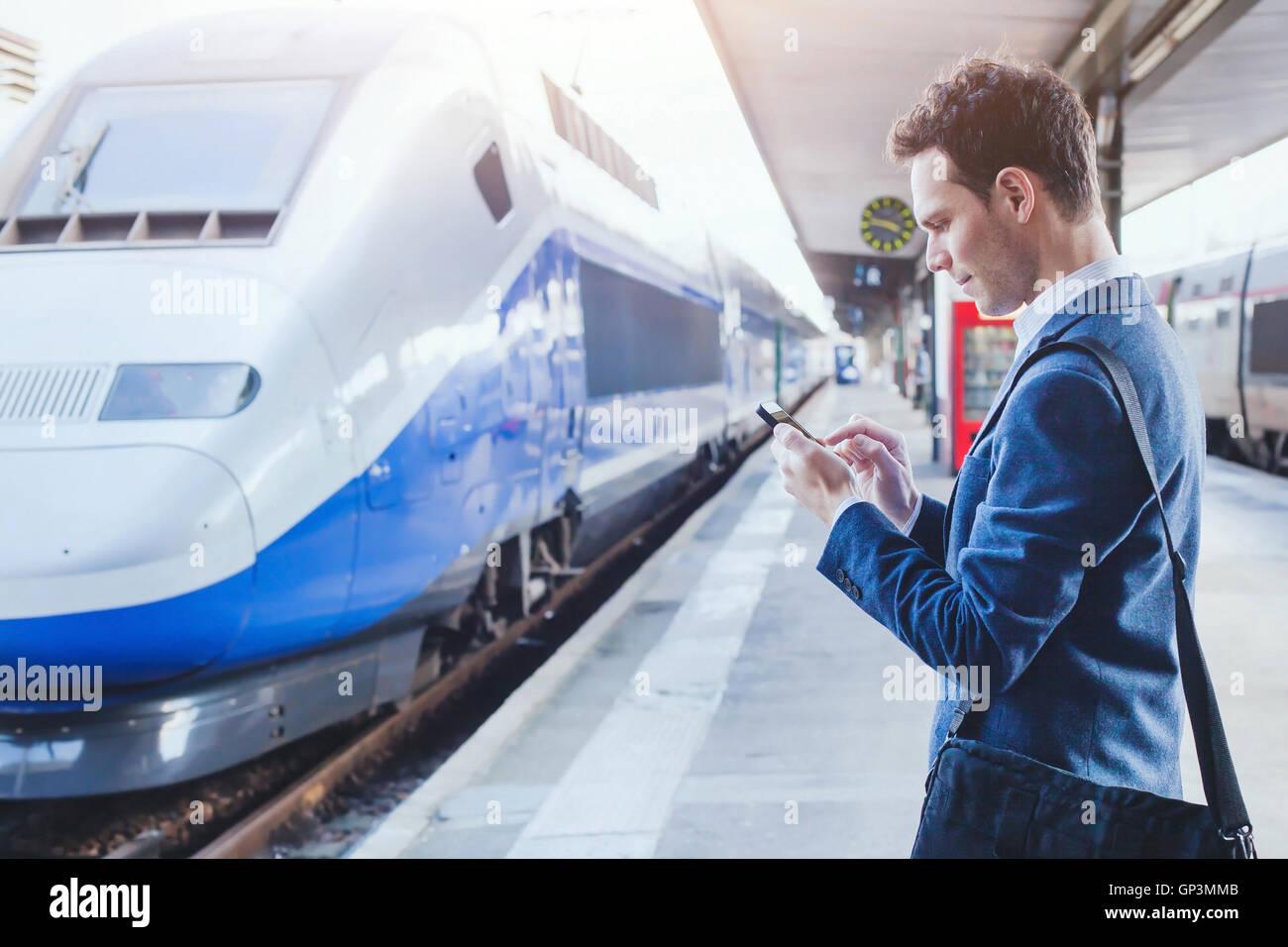 Hombre utilizando aplicaciones móviles en su smartphone en la estación de tren, los viajes de negocios Foto de stock