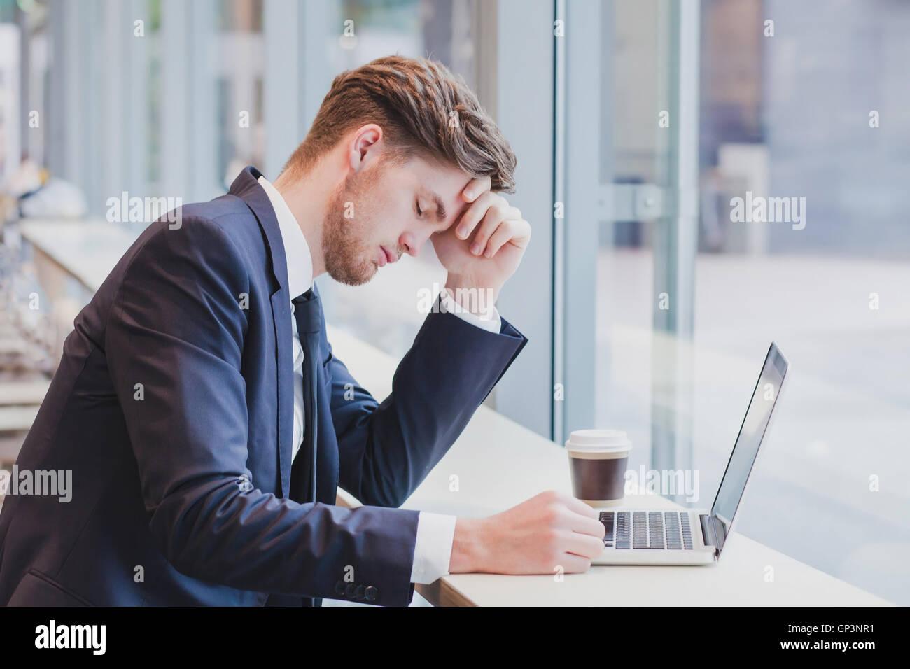 Dolor de cabeza, cansado hombre de negocios cerca de laptop Imagen De Stock