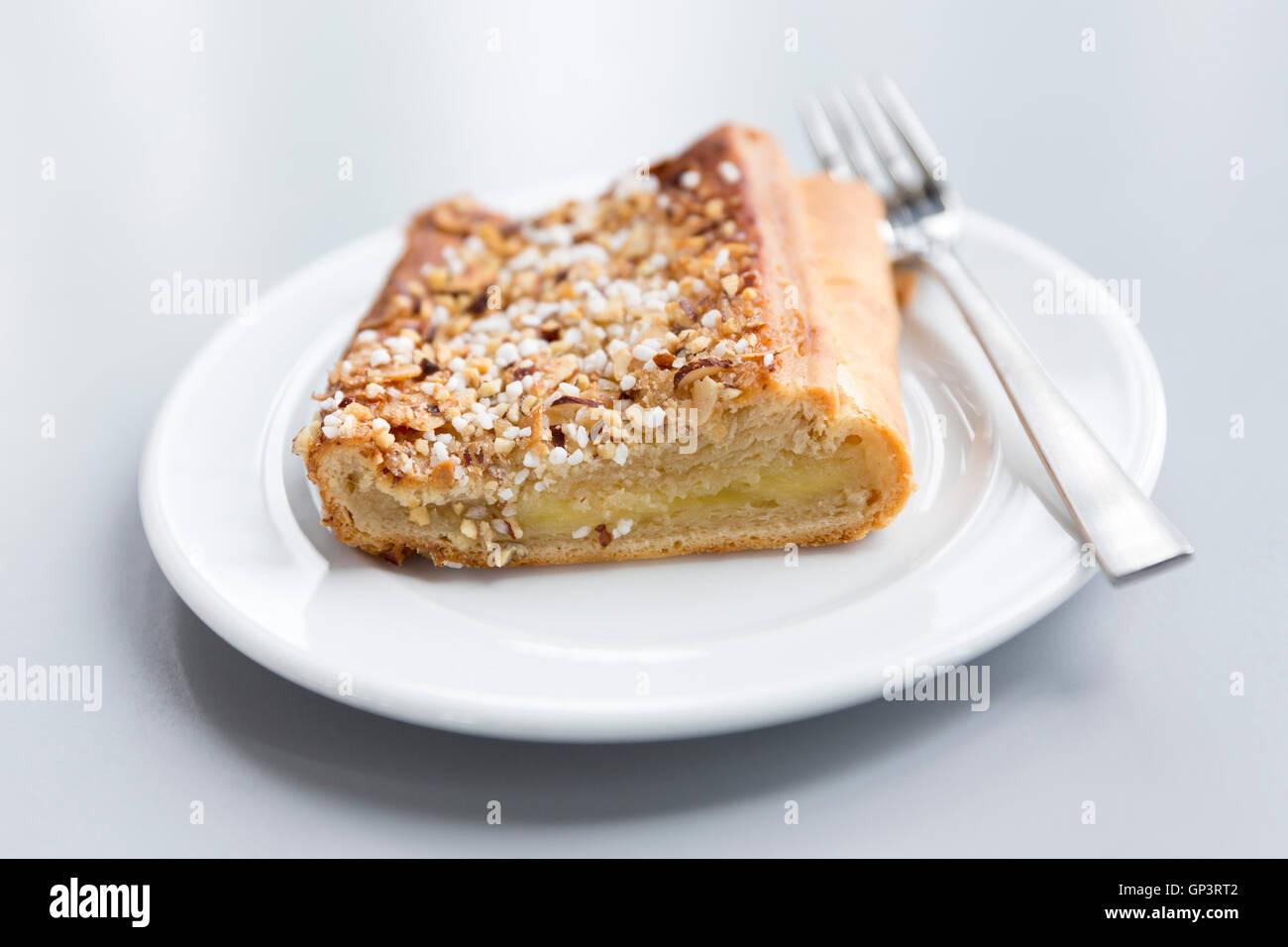 Pastas danesas sobre placa blanca con horquilla - dulce tradicional tarta de manzana con nueces y azúcar, especialidad Imagen De Stock
