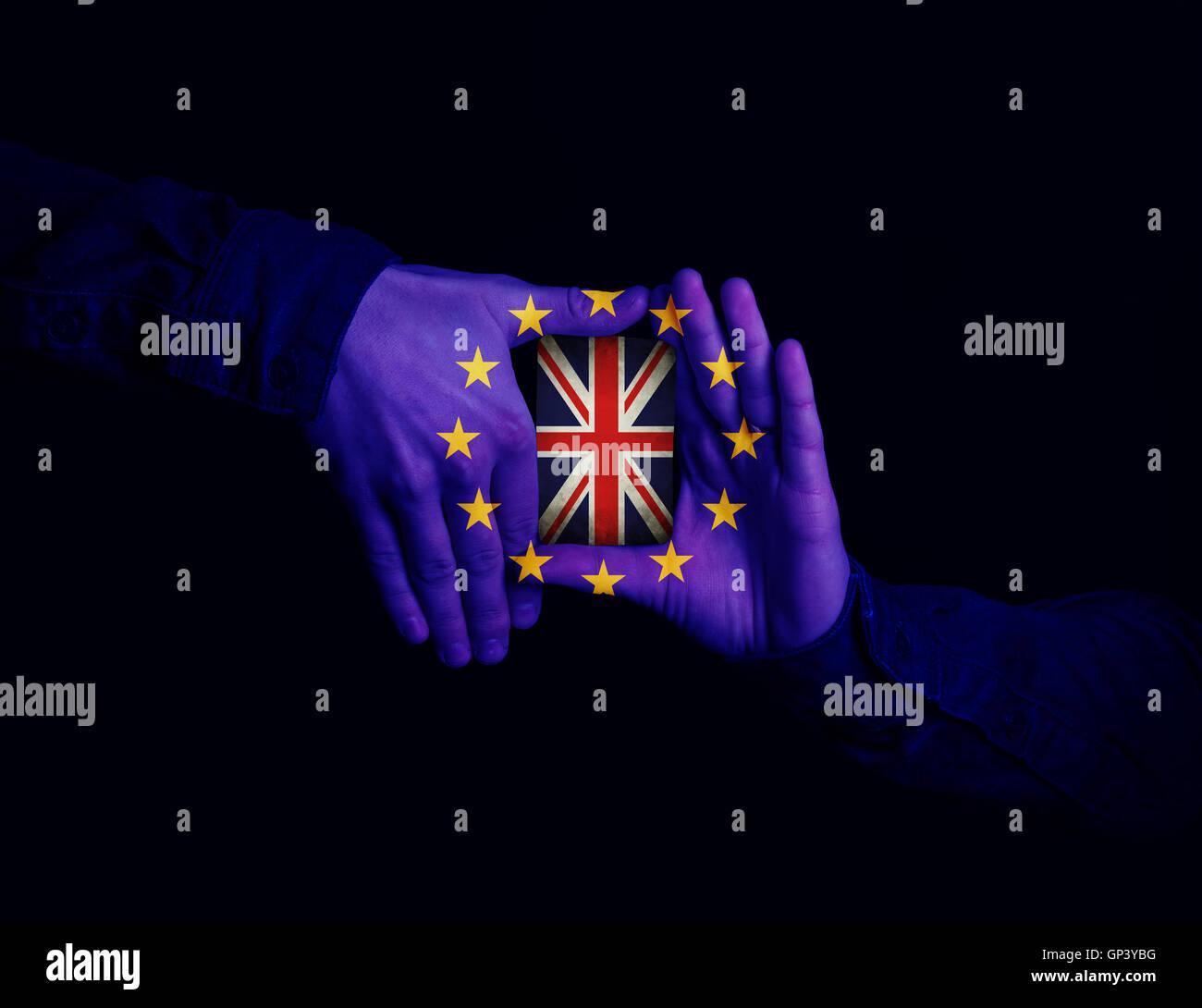 Cerca de manos atada con la bandera de la Comunidad Europea mantiene una tarjeta con la bandera del Reino Unido. Imagen De Stock