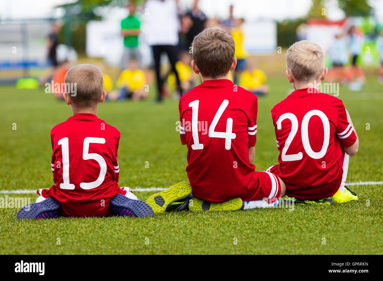 5a9edfe81f68a Los muchachos en el equipo de fútbol sentados juntos en el campo de  deportes. Los
