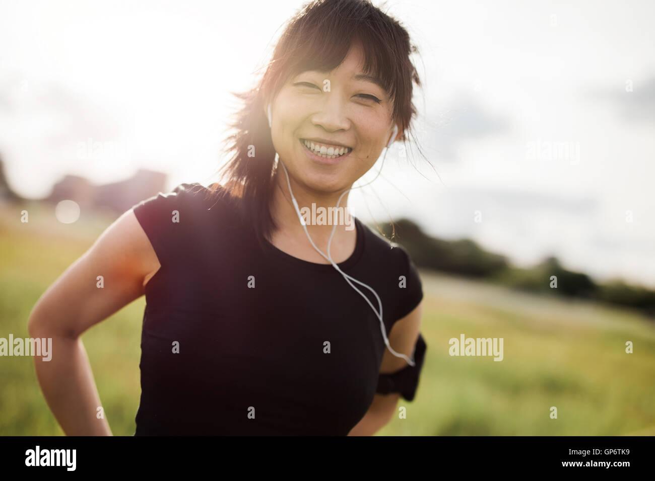 Retrato de mujer feliz corriendo al aire libre permanente y sonriendo a la cámara. Modelo femenino chino en Imagen De Stock