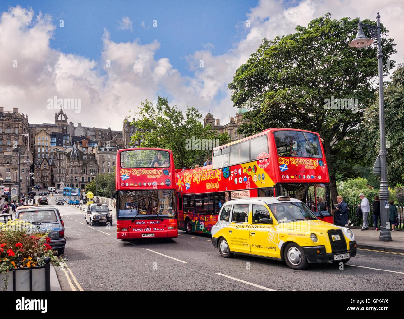 Los autobuses turísticos y un taxi amarillo en Waverley Bridge, Edimburgo, con vistas al casco antiguo de la Imagen De Stock