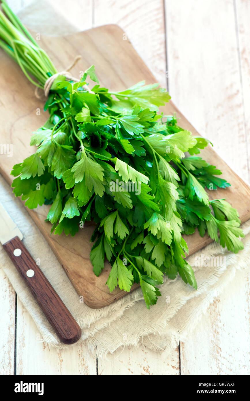 Perejil italiano orgánicos closeup sobre mesa de madera rústica, saludable comida vegetariana Imagen De Stock