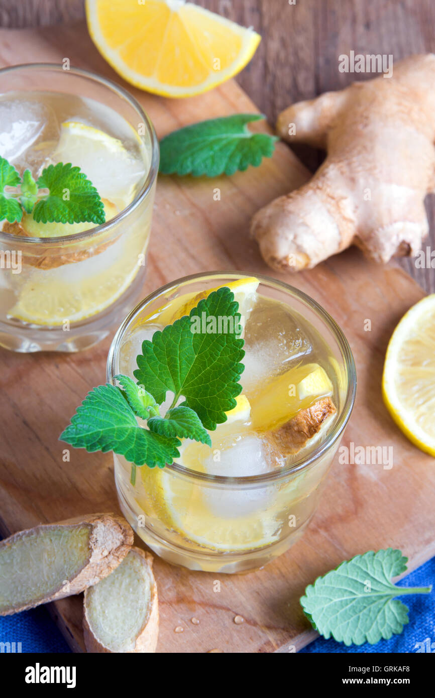 Ginger Ale soda con limón, menta, jengibre y hielo sobre fondo de madera rústica Foto de stock