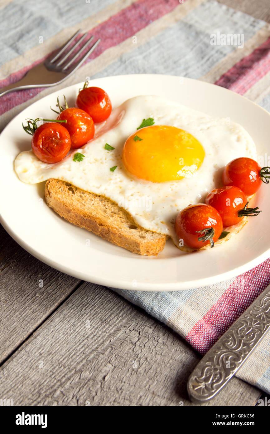 Huevo frito en pan y tomate frito para desayunar en la placa y tabla rústica Imagen De Stock