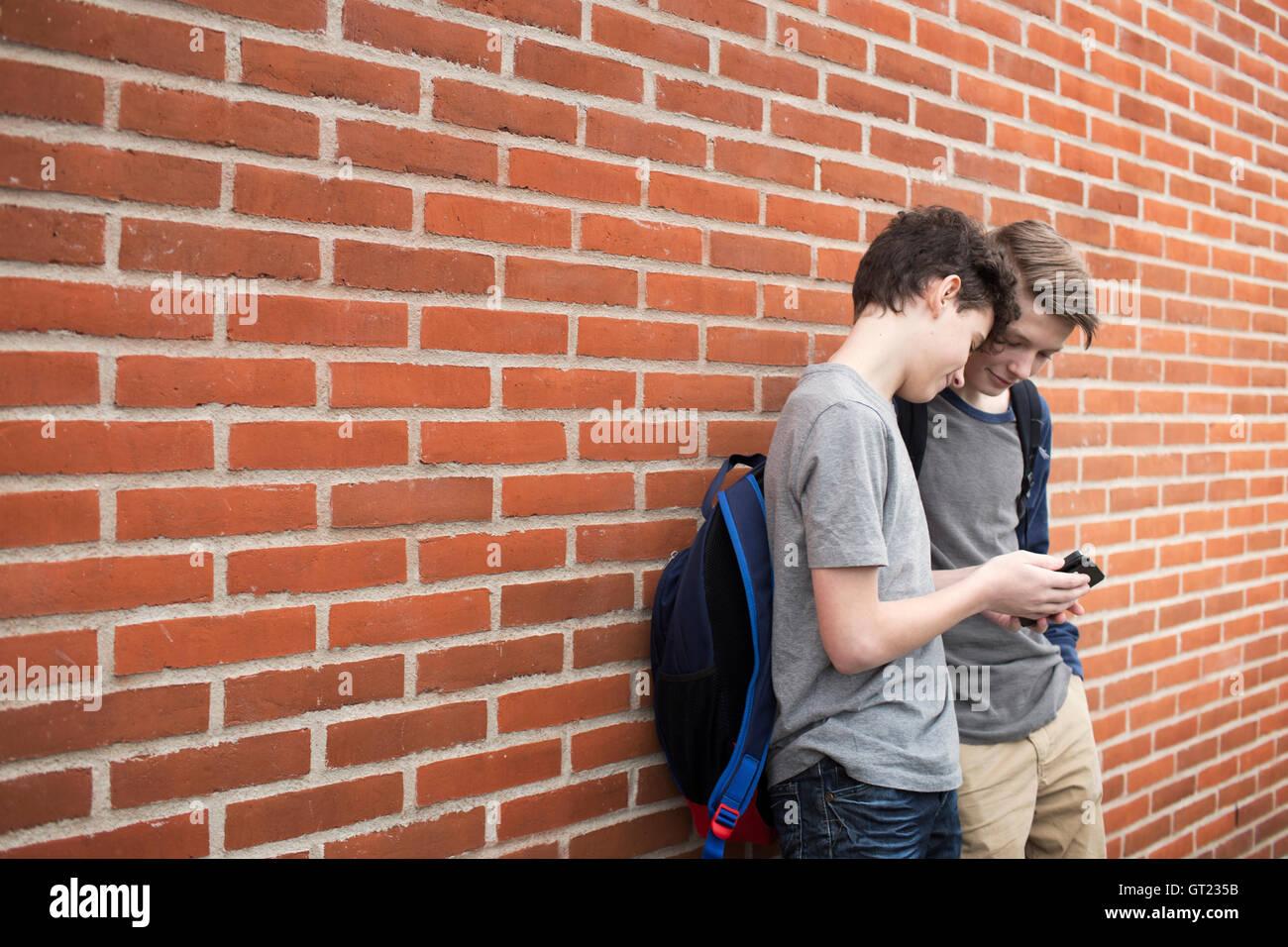 Los colegiales (12-13) con el teléfono móvil en la parte delantera del edificio Foto de stock