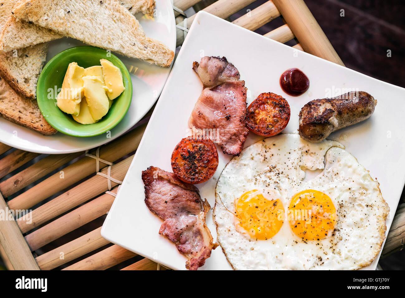 Inglés británico clásico desayuno con huevos fritos bacon y salchichas tomate tostadas set Imagen De Stock