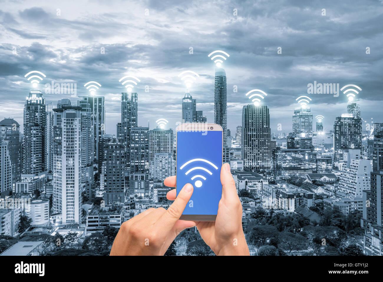 Mano sujetando el teléfono móvil con la red de conexión de red wifi. Concepto de conexión de Imagen De Stock