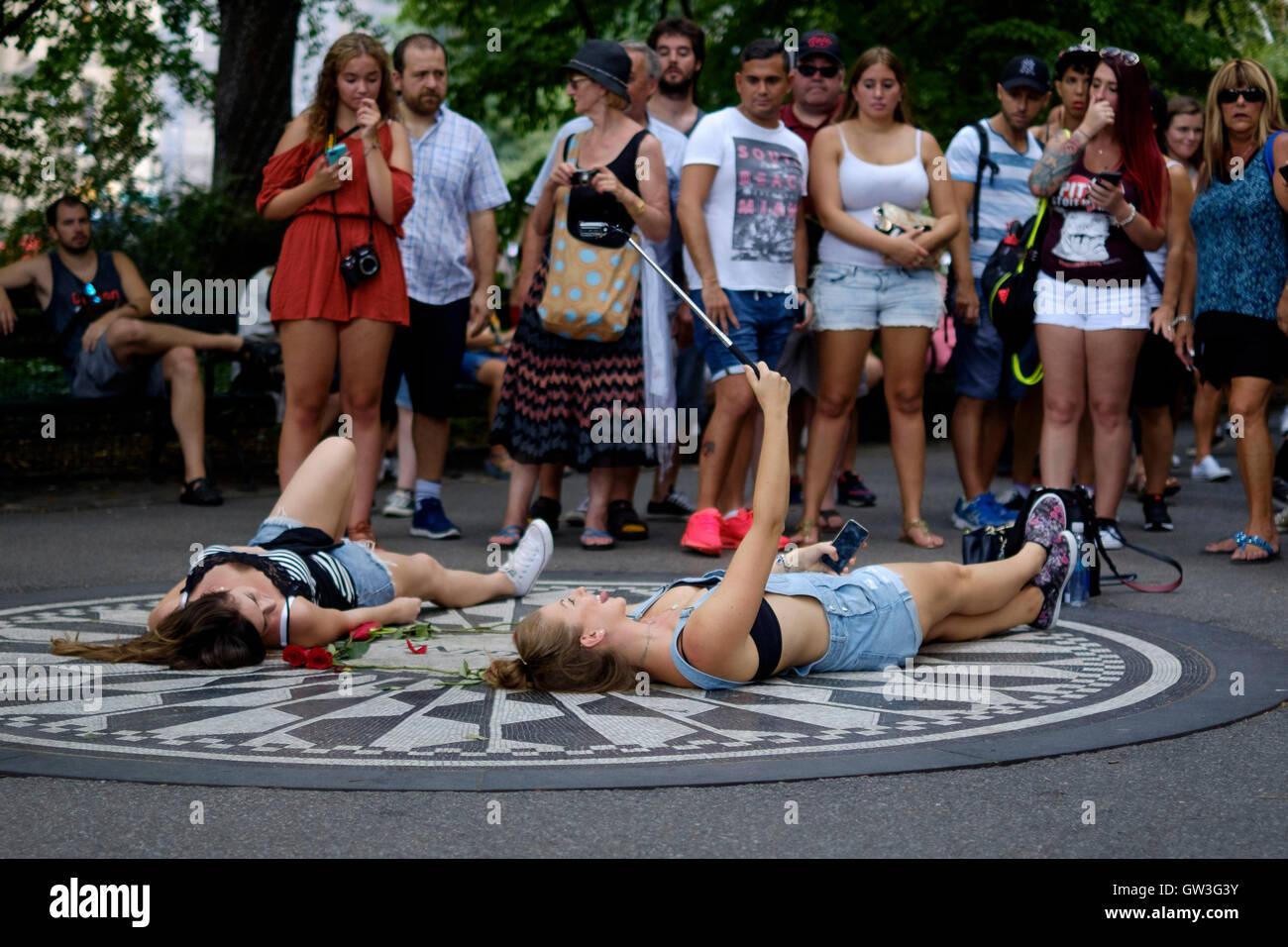 Dos mujeres jóvenes (jóvenes) sentar en el memorial de John Lennon imagine en Central Park y tomar un selfie. Otros Foto de stock