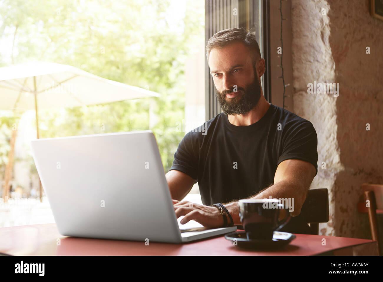 Guapo empresario barbudo vistiendo negro Tshirt portátil de trabajo Tabla de madera Urban Cafe.Joven Manager Imagen De Stock
