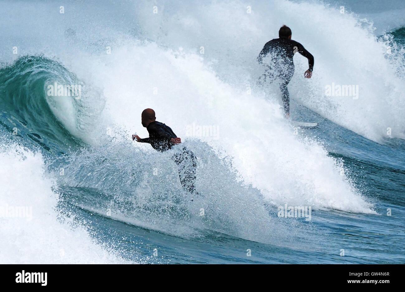 Dos hombres de traje negro surfistas surf espectaculares olas rompiendo en la playa Fistral curling Imagen De Stock