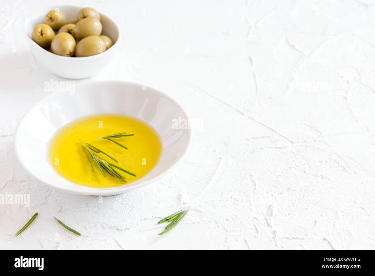 Aceite de oliva orgánico con romero sobre fondo de piedra blanca con copia espacio, concepto de comida saludable Imagen De Stock