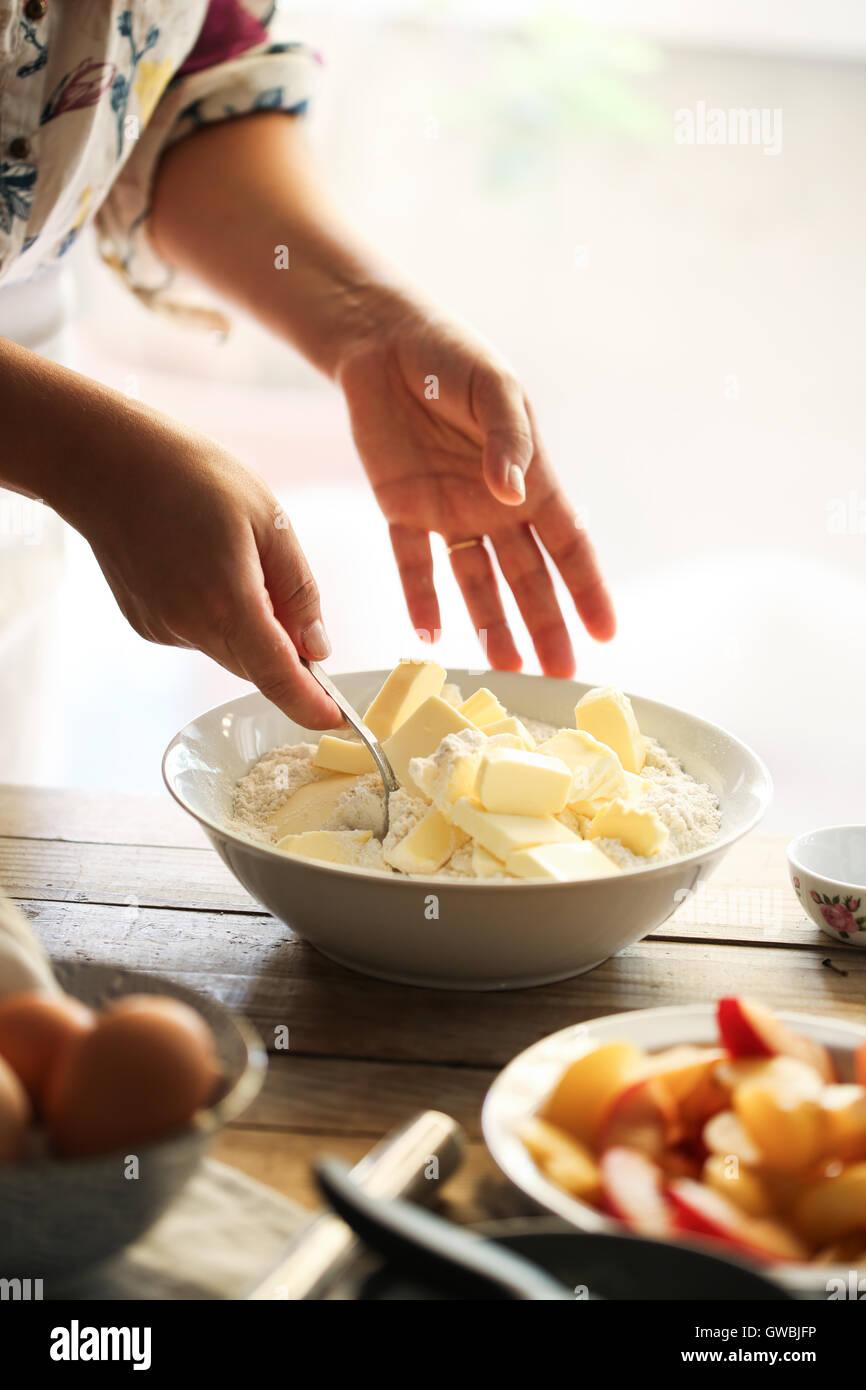 Mujer miking mantequilla y harina. Imagen De Stock