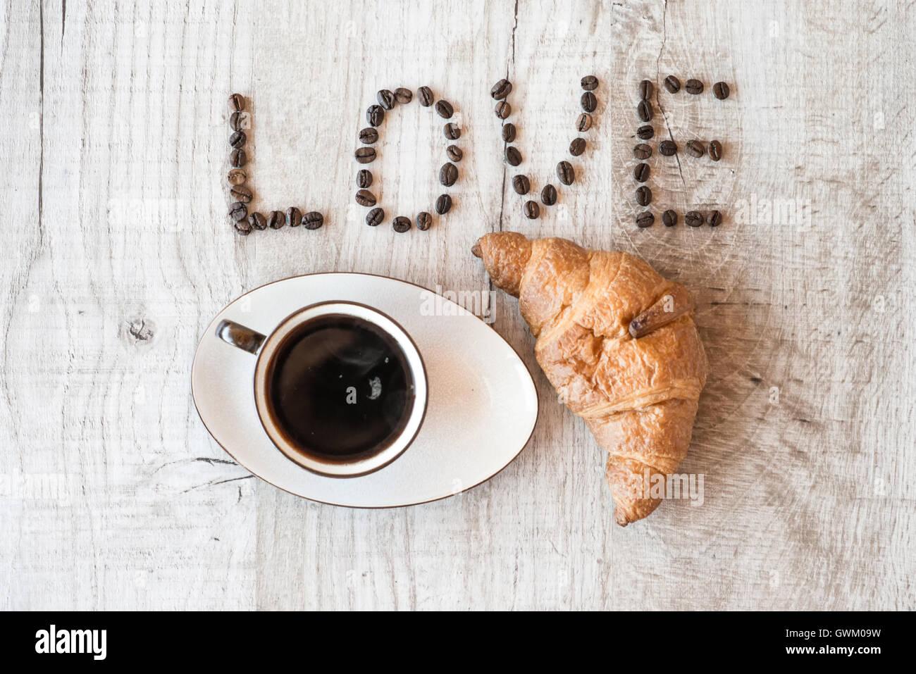 Taza de café con croissant. título me encanta el café. Imagen De Stock