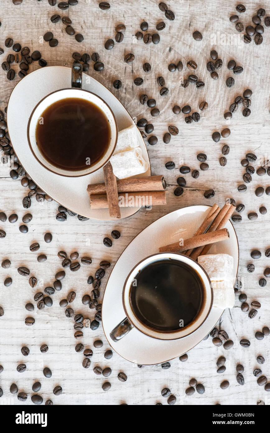 Taza de café con cereales, croissant, delicias turcas y palitos de canela sobre fondo de madera Imagen De Stock