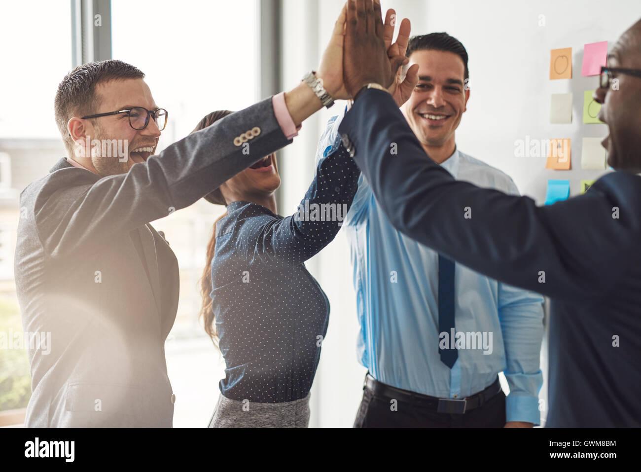 Feliz éxito multirracial equipo empresarial dando una alta cincos gesto como se ríen y alegrar su éxito Imagen De Stock