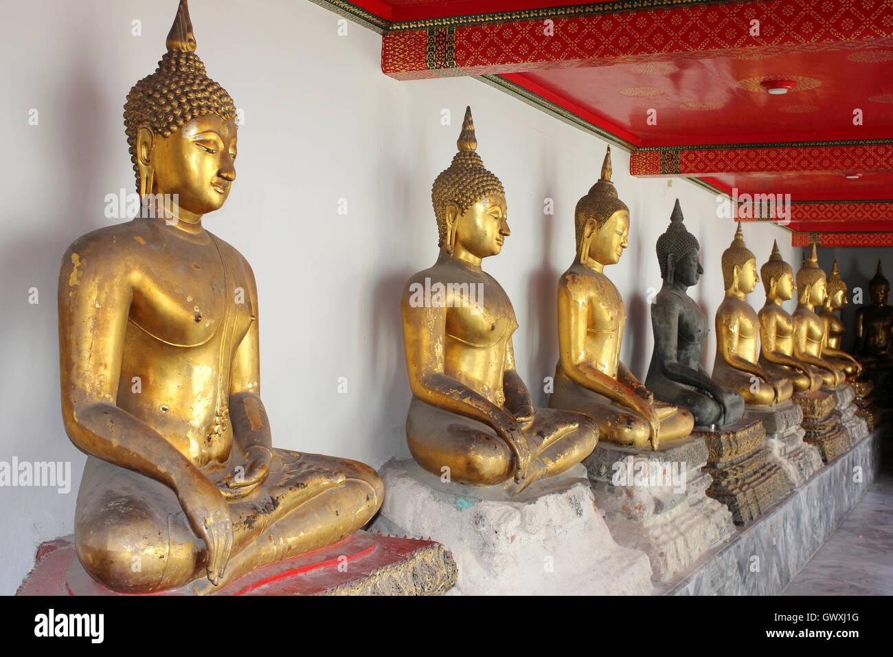 Línea de Budas sentados en el templo Wat Pho, en Bangkok, Tailandia Imagen De Stock