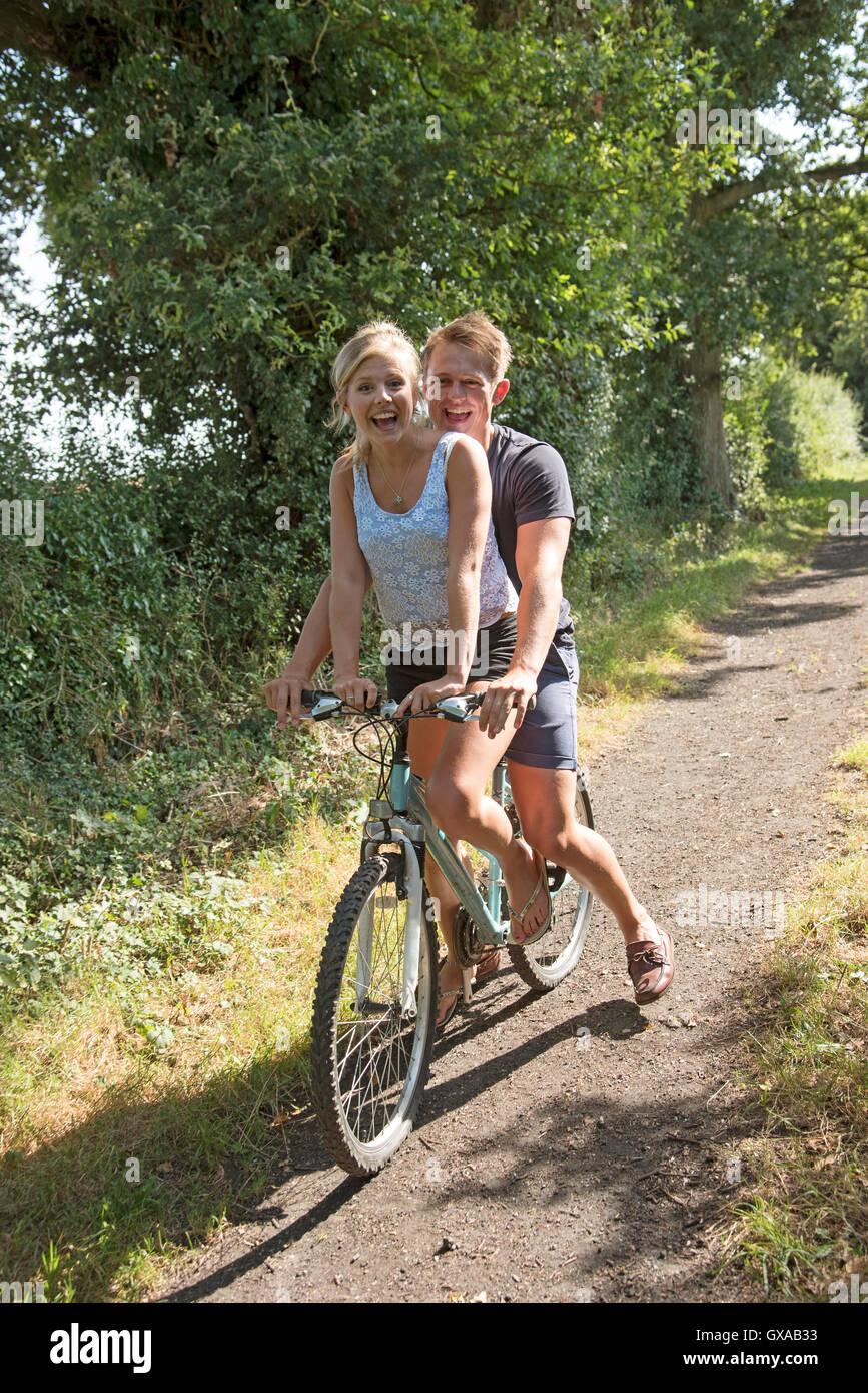 Par bicicleta - Adolescentes compartir a lo largo del ciclo un país Inglés Lane Foto de stock
