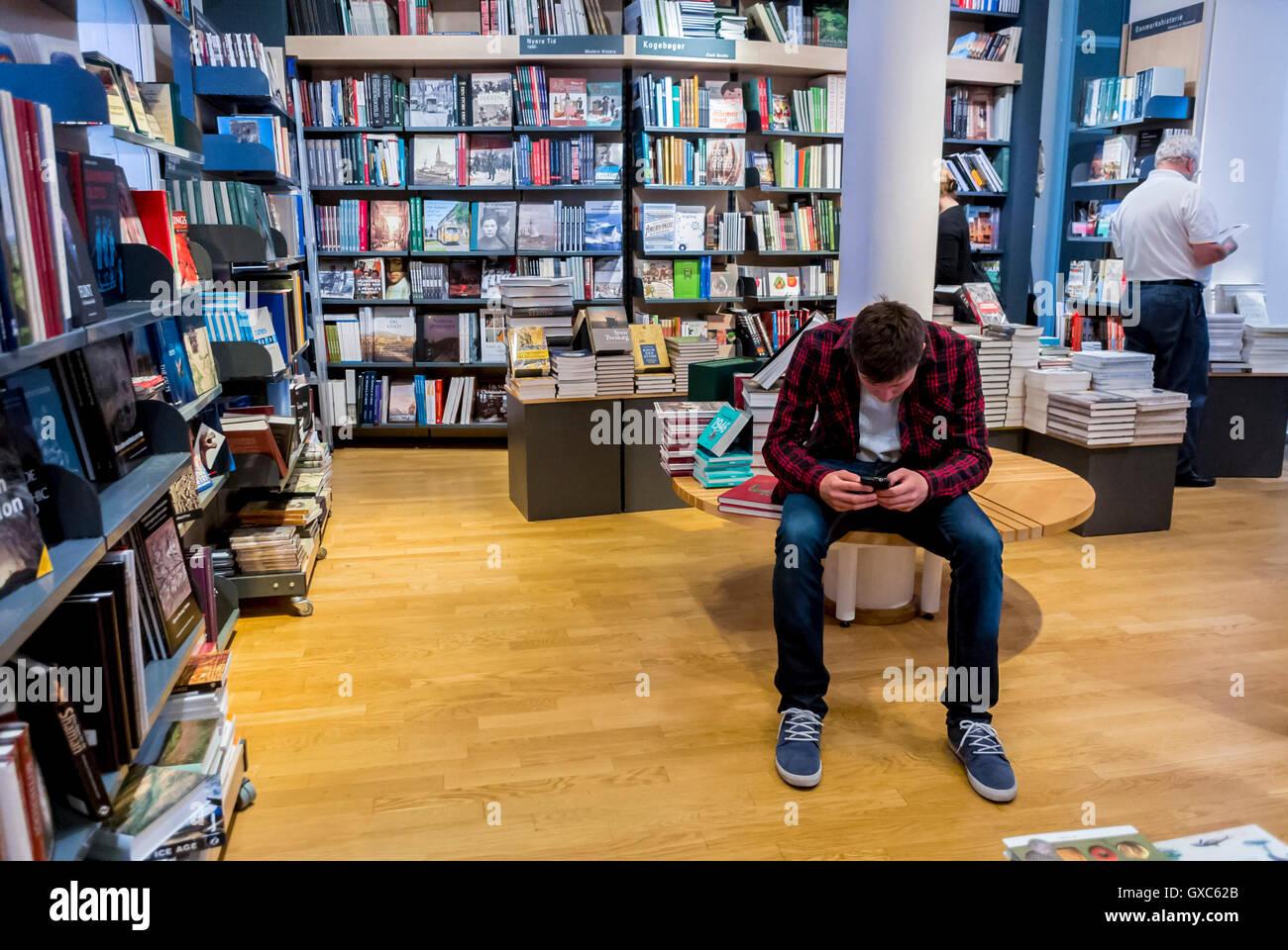 Copenhague, Dinamarca, en el interior, el Museo Nacional Nationalmuseet, Teen mirando Smart Phone en Bookstore Foto de stock