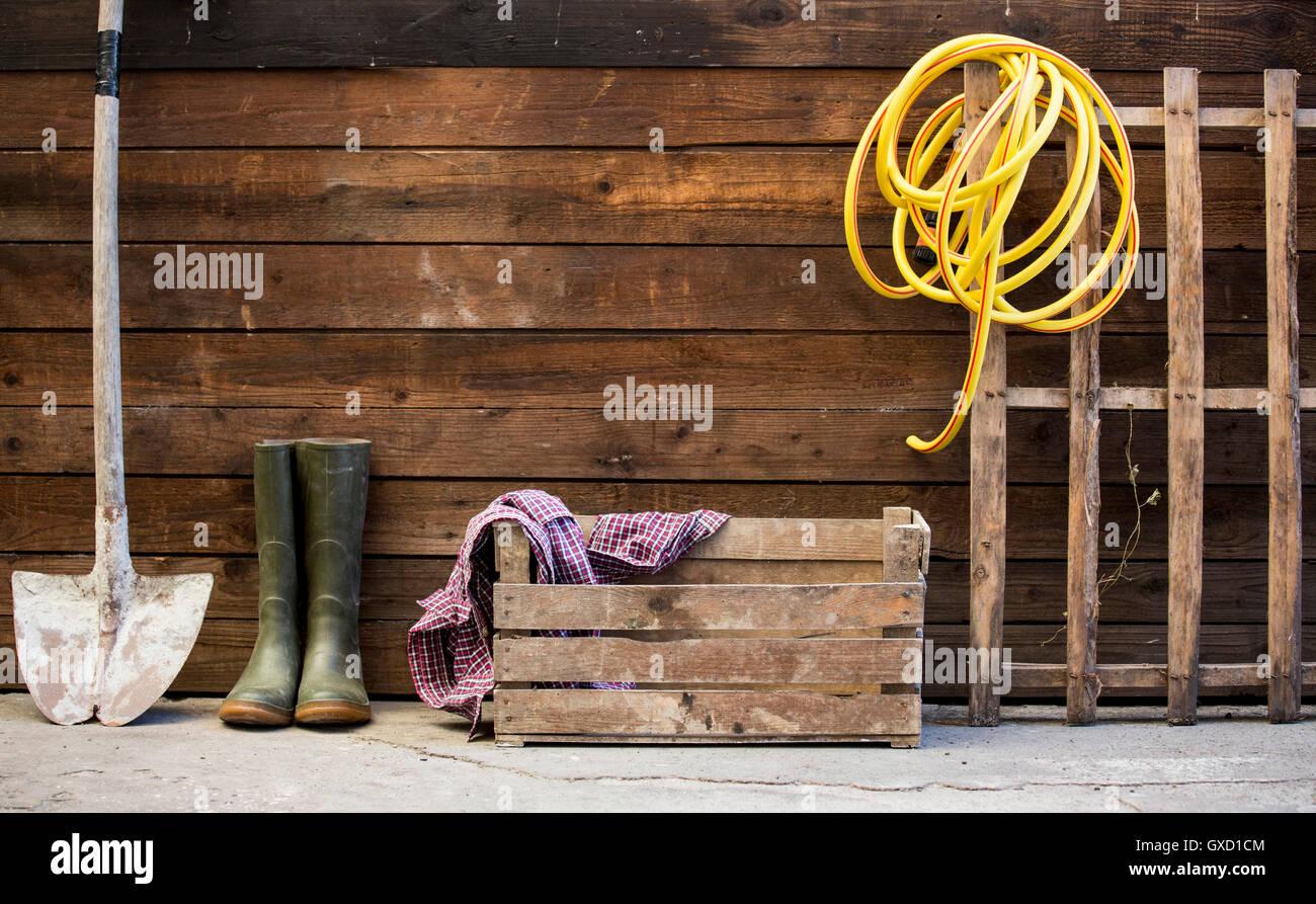 Fila de pala, botas de goma y la manguera por arrojar Foto de stock