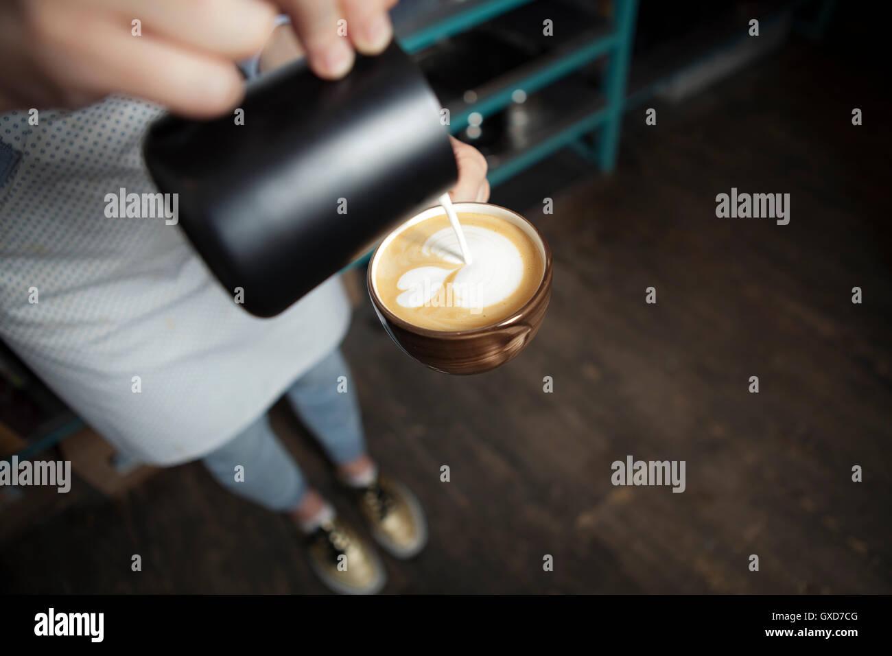Cómo hacer latte arte por barista centrarse en leche y café Imagen De Stock