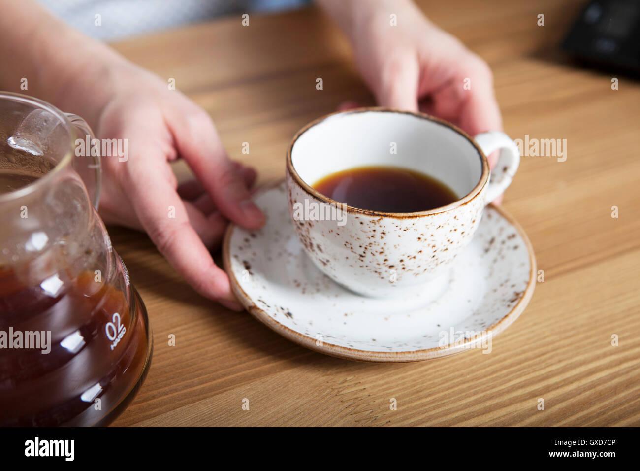 Blanco taza de café en la mano. Barista celebración café Imagen De Stock