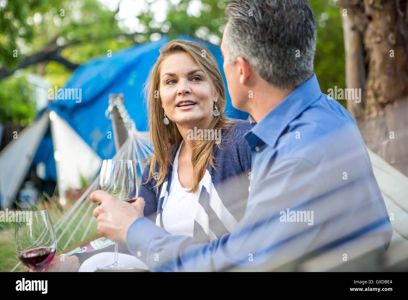 Pareja conversando en la hamaca en el garden party Imagen De Stock