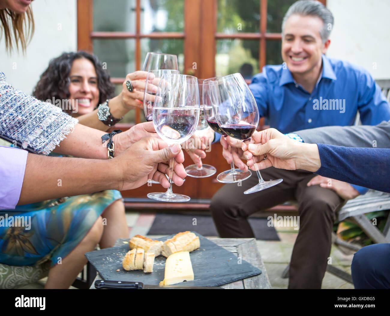 Los adultos maduros amigos vino brindis a la fiesta en el jardín en el patio Imagen De Stock