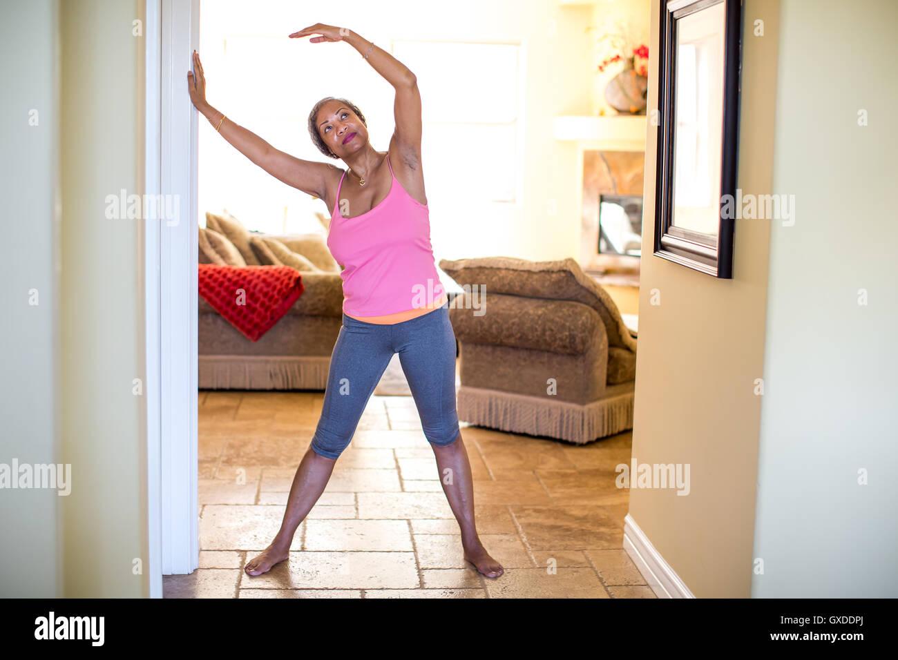 Mujer con brazos levantados haciendo ejercicio de estiramiento Imagen De Stock