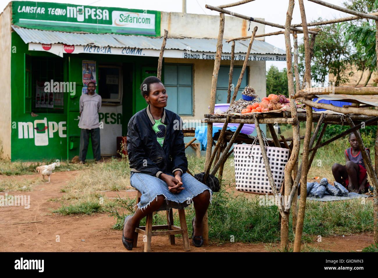 KENIA, Condado de Siaya, aldea Kotanega, tienda M-PESA, de compañía Safari.com una joint venture de Vodafone y telefónica keniana, pago por teléfono móvil, mercado mujer vende verduras / Kenia, bezahlen por Mobiltelefon, M-Pesa von Safari.com una joint venture von Vodafone y telefónica keniana, Marktfrau verkauft Gemuese Foto de stock
