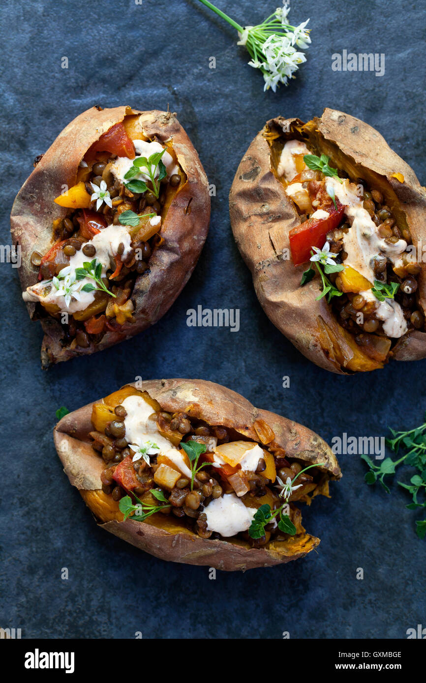La batata con lentejas picantes, pimiento amarillo y relleno de tomate, tomillo, flores de ajo y chipotle crema Imagen De Stock