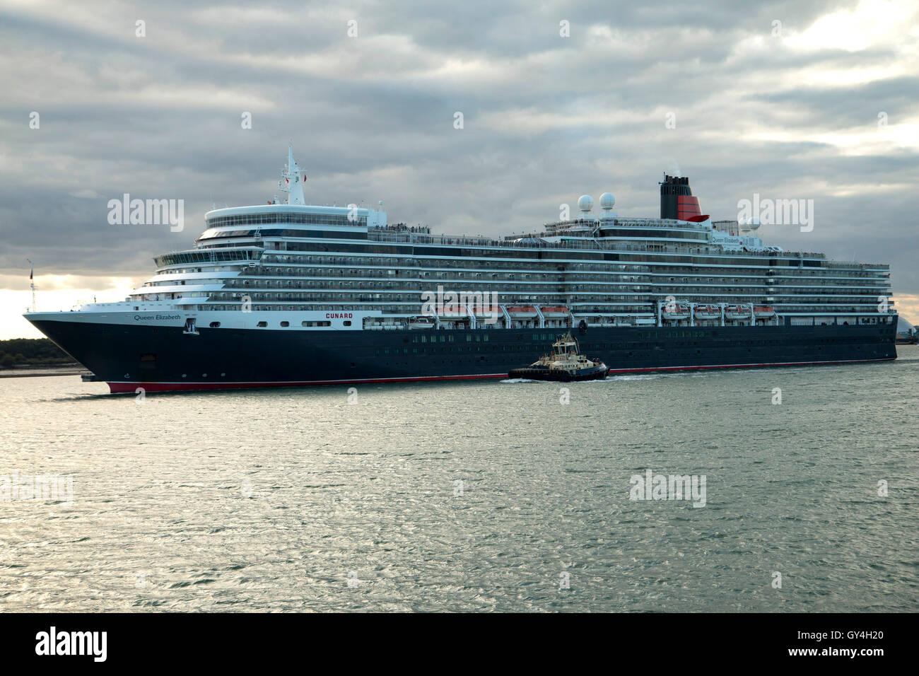 Cunard Cruise Ship Queen Elizabeth dejando Southampton en ruta a Lisboa el 16 de septiembre de 2016 con un remolcador Foto de stock