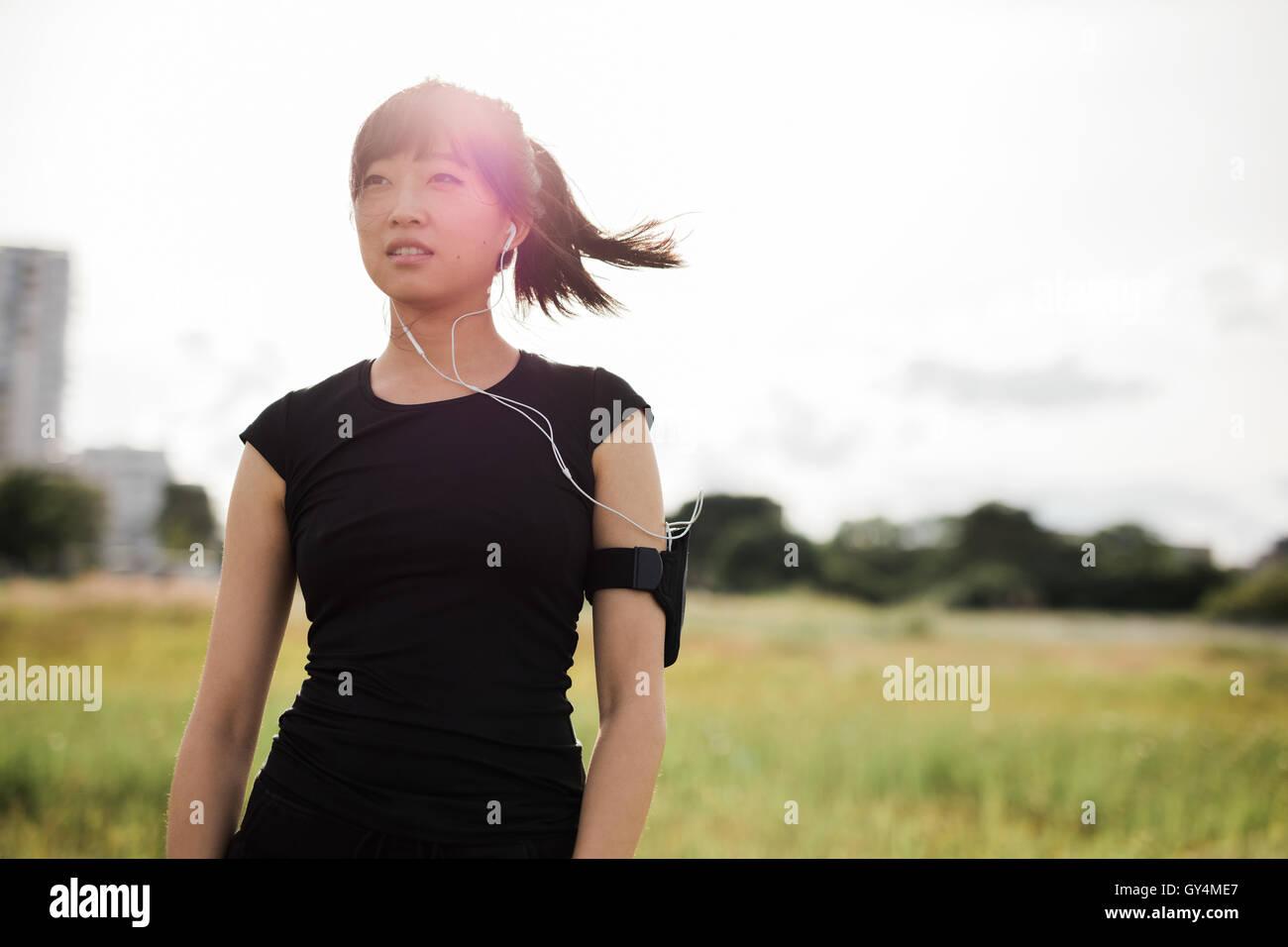 Foto de joven mujer en ropa deportiva de pie afuera en el parque de la ciudad en día soleado y apartar la mirada. Imagen De Stock