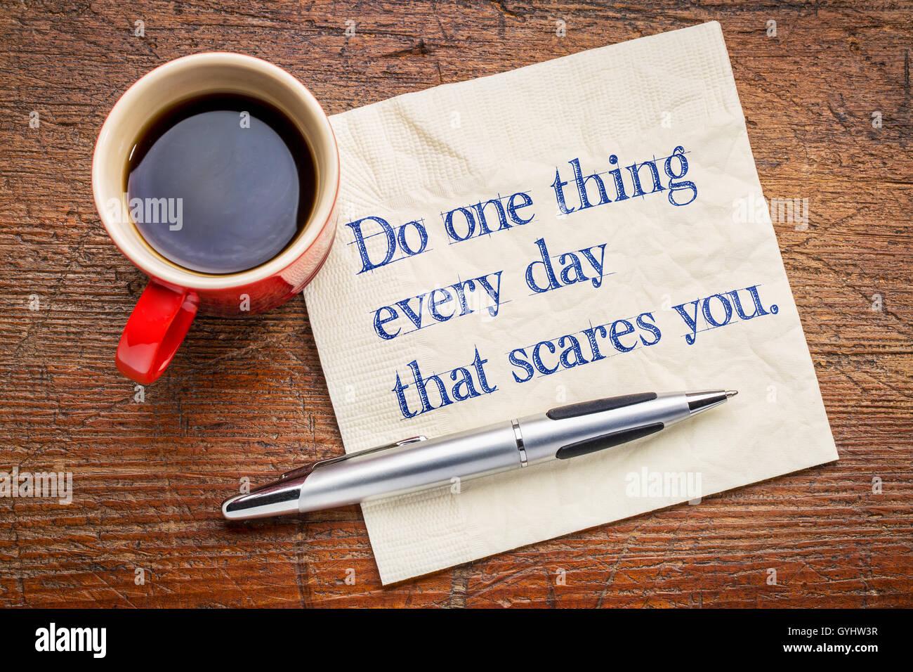 Hacer una cosa cada día que le asusta a usted - escritura motivacional en una servilleta con una taza de café Imagen De Stock